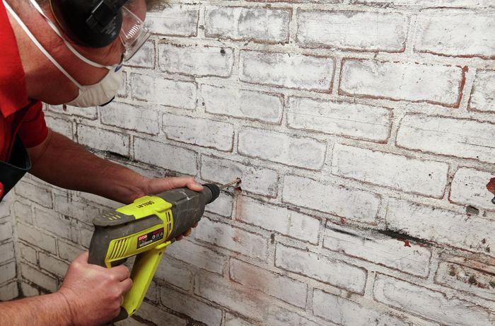 Person drilling into a wall.