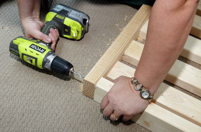 Person drilling timber bed slats into timber beam