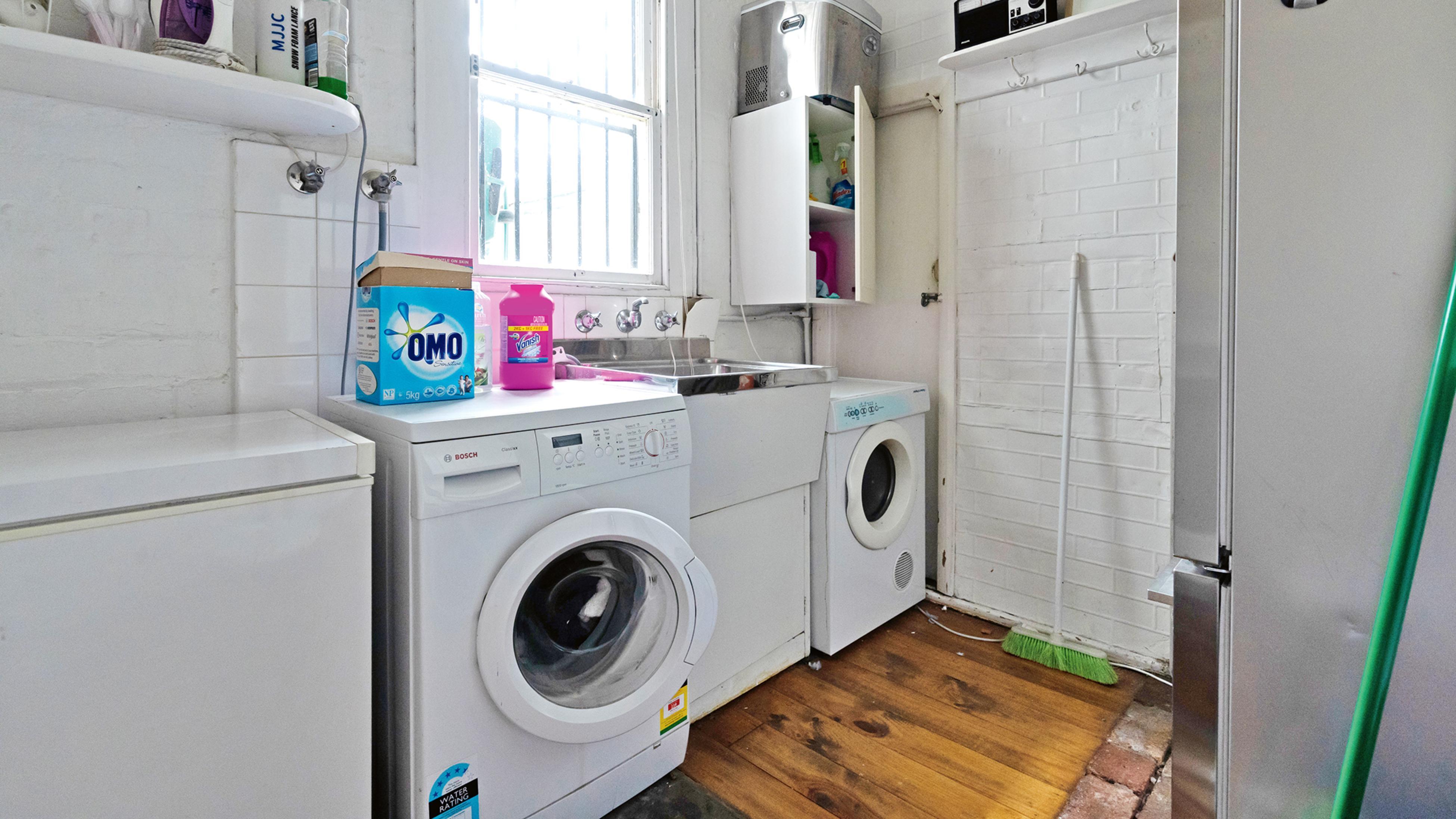 Old laundry with bland colour scheme featuring washing machines, dryers and shelves full of detergent and other cleaning products.