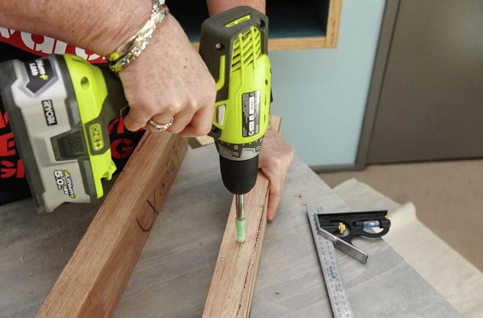 A person drilling a hole in a piece of timber