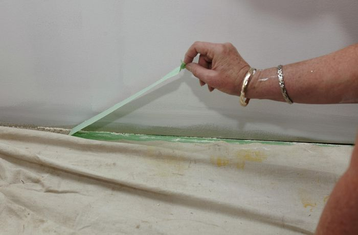 Painter's tape being pulled up from the carpet
