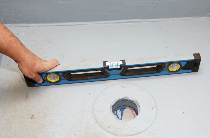 A person holding a spirit level on a shower base