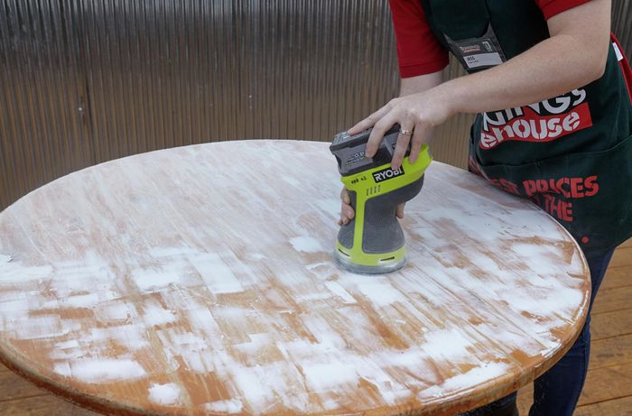 A varnished table being sanded down for a smooth surface