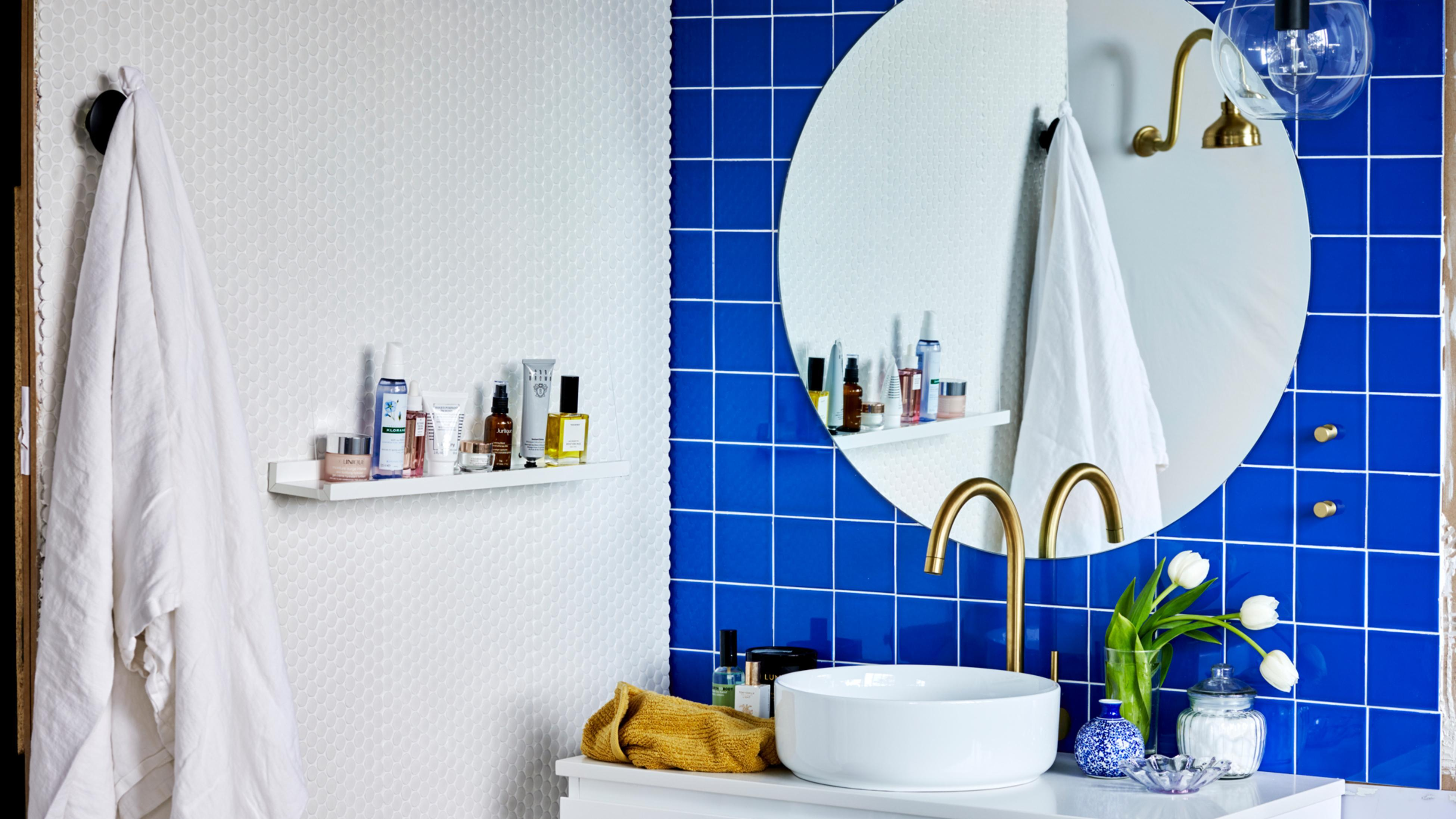 Bathroom with interesting blue and white tiled walls, gold tapware.
