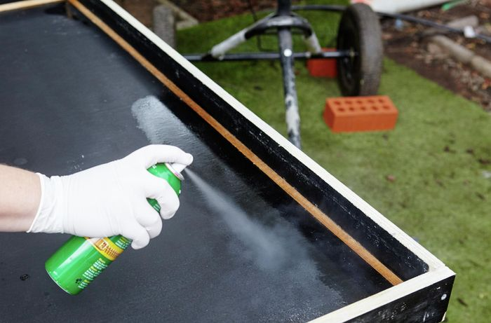Person silicon spraying inside of form ply frame.