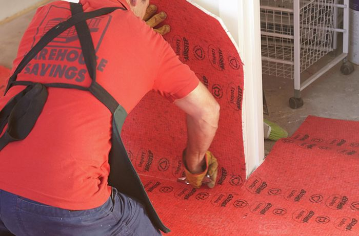 Underfelt being secured to the floor with staples and a hammer