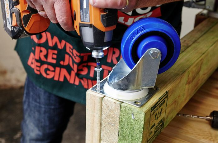 A person attaching a castor wheel to pine framing timber using a cordless drill