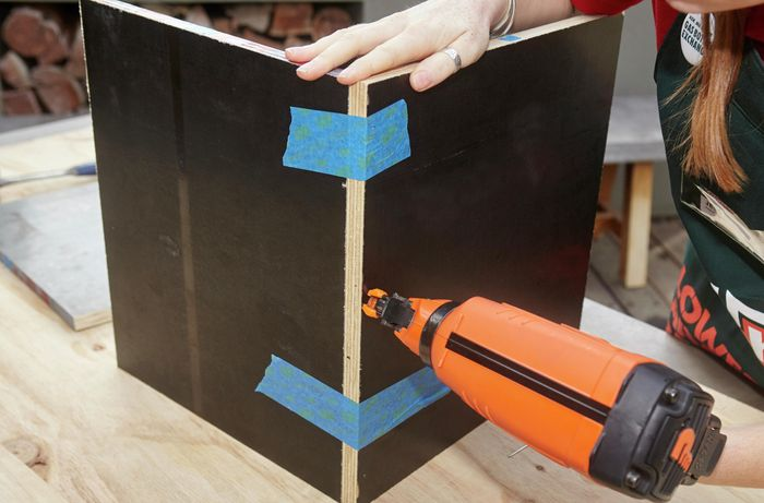 Two side panels of a wooden storage box being nailed together with a nail gun