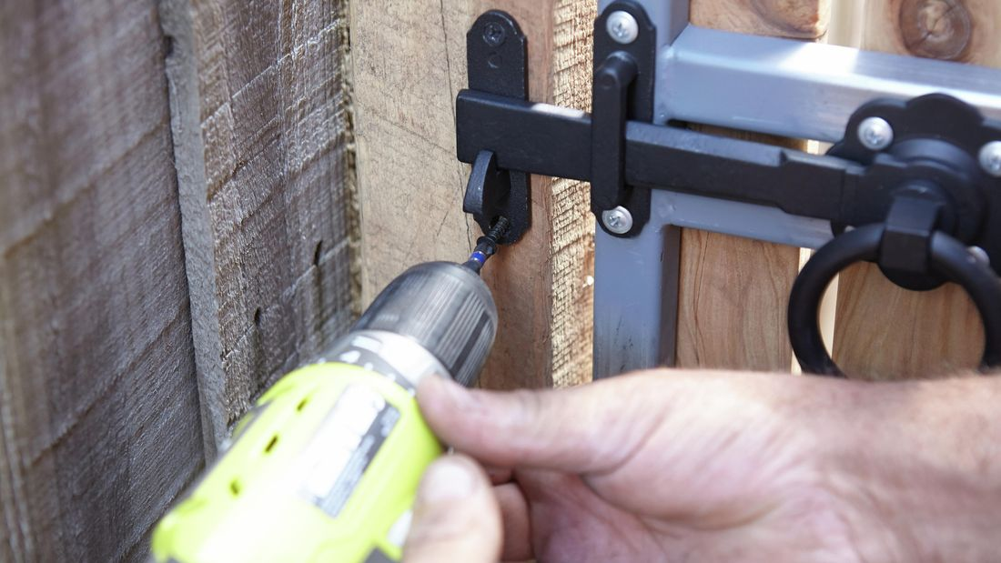 Person screwing a catch plate to a gate post using a cordless driver