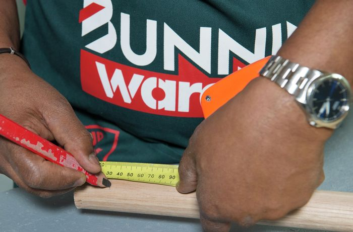 A person marking a length of timber using a measuring tape and pencil