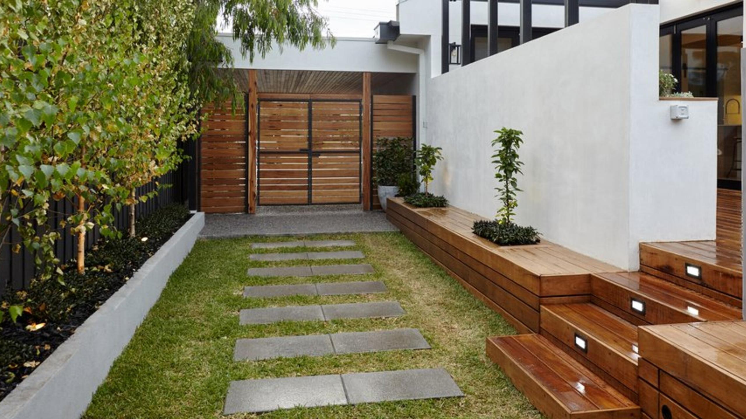 Garden area with glass, walls and trees.
