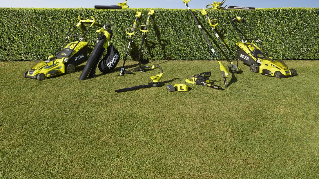 A range of RYOBI equipment and power tools laid out on a lawn.