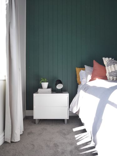 Grey-carpeted bedroom with bed and white bedside table