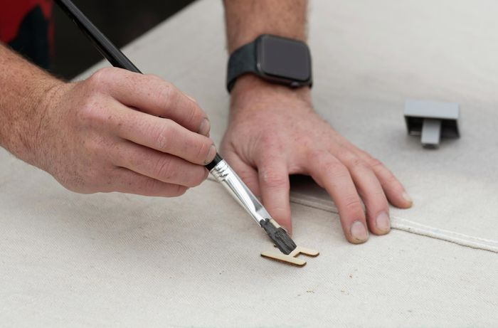 A wooden letter H being painted black with a paintbrush