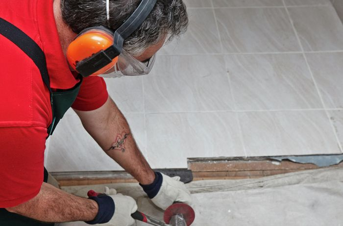 A person wearing protective gear using a hammer and bolster to lever up floor tiles