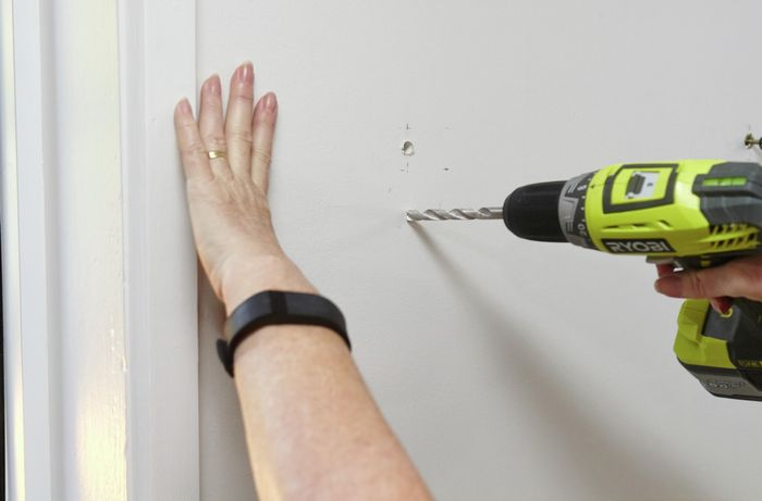 A person drilling holes in a plasterboard wall