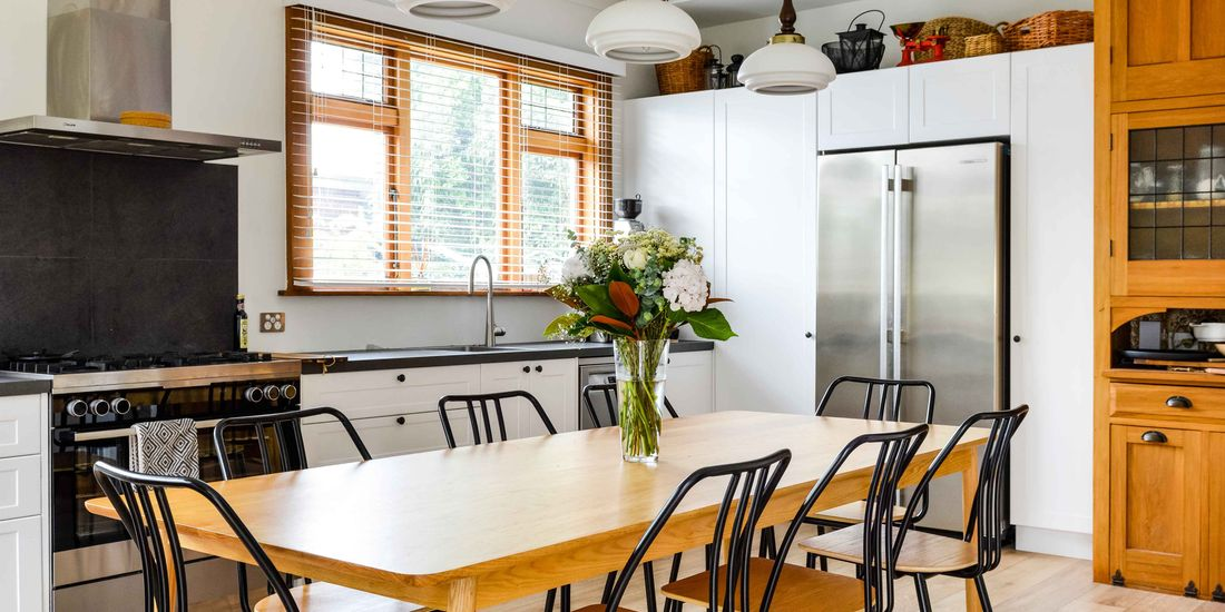 Neat and clean kitchen with a dining table with a vase of flowers