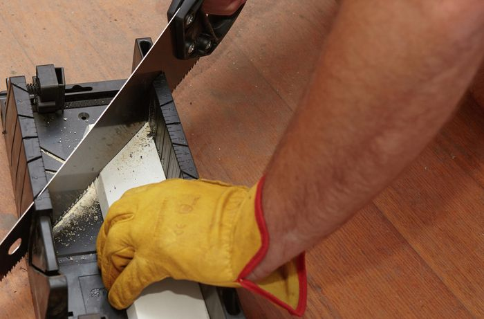 A person cutting architrave with a hand saw and mitre box