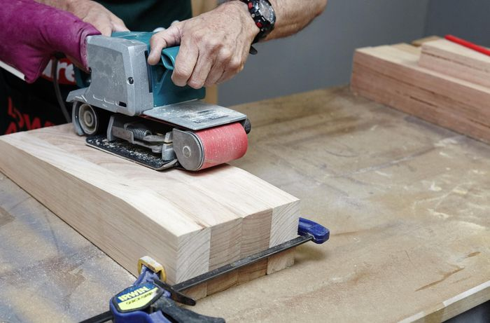 The four legs of a wooden chair being sanded down with a belt sander, held together with a clamp