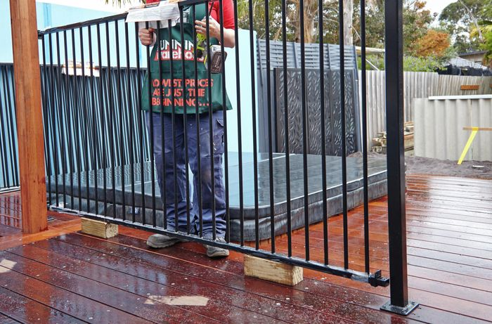 Person holding an aluminium fence.