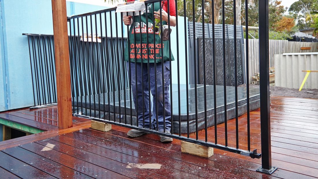 Person holding black pool fence with two hands.
