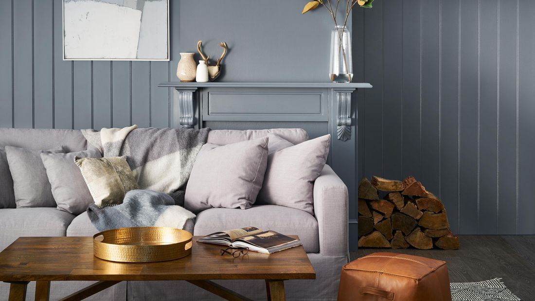 Lounge room  with grey walls, side table with vase and print hanging on the wall