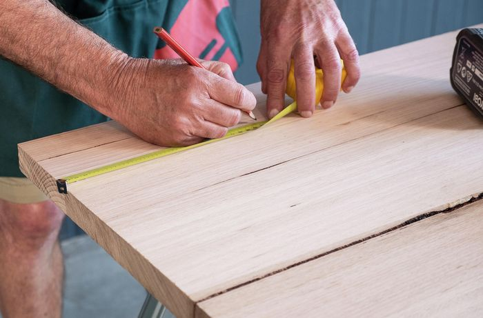 A desk top being measured to mark out drill points for desk leg screw points
