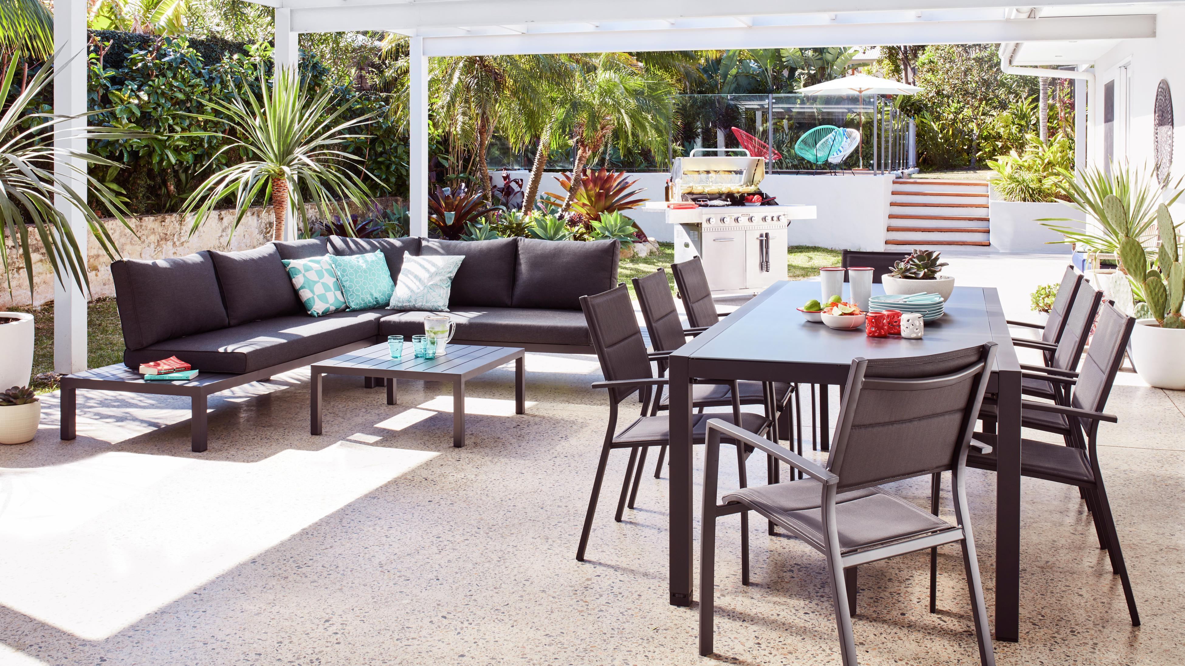 Covered outdoor dining area with dining table and outdoor lounge