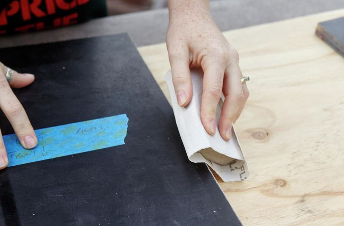 The sides of a piece of timber being smoothed with sandpaper