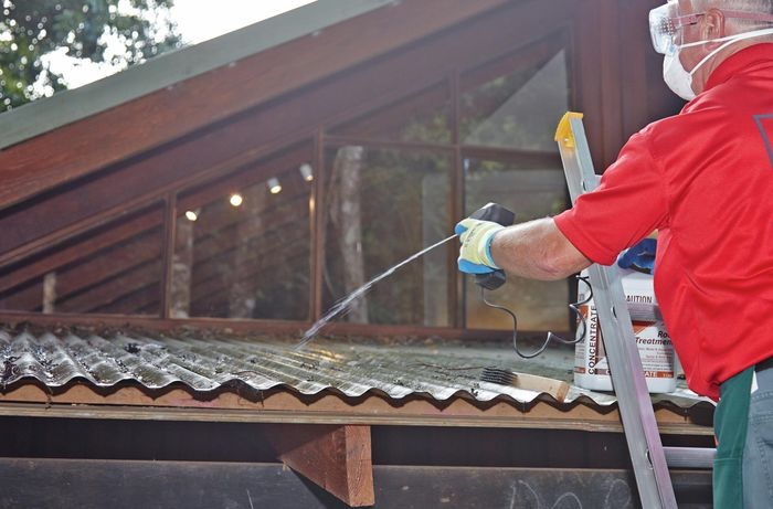 Person on a ladder wearing protective clothing spraying roof with a cleaning solution