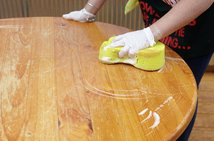 A table being prepared for painting with a deep clean with a sponge and soapy water