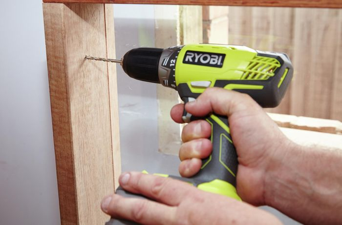 Drilling pilot holes into the window frame