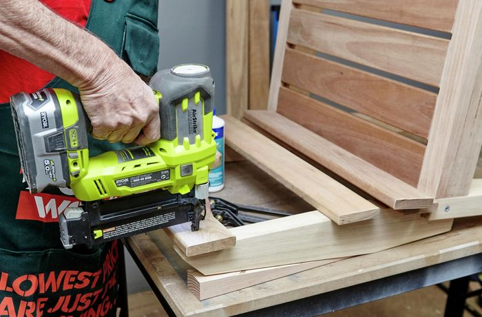 A wooden plank being nailed to a chair with a nail gun as part of a chair's backrest