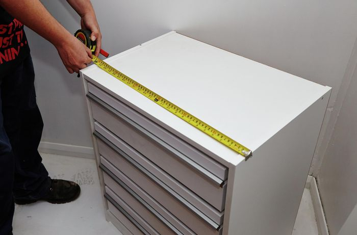 Person using measuring tape to measure length of wardrobe insert unit.