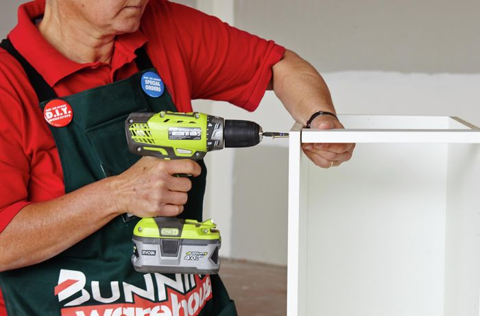 Person attaching cabinet rail using a drill