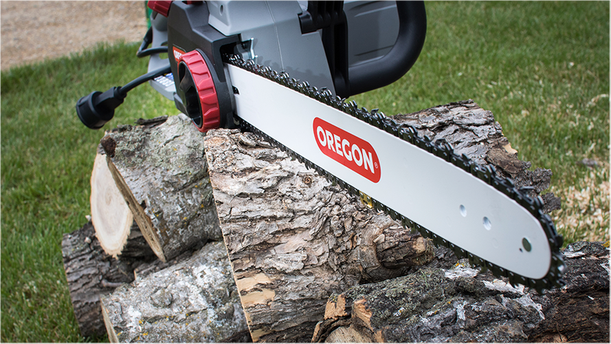Chainsaw sitting on stack of logs