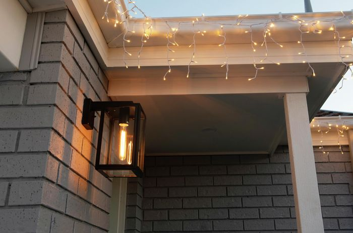 An entry porch with entry light and a string of fairy lights