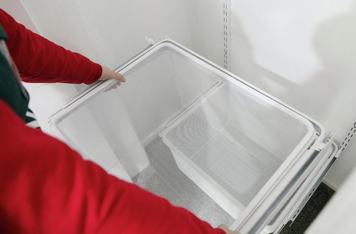 Person sliding storage organiser into cupboard