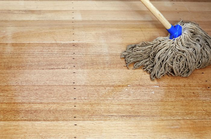 A hardwood timber floor being cleaned with a mop