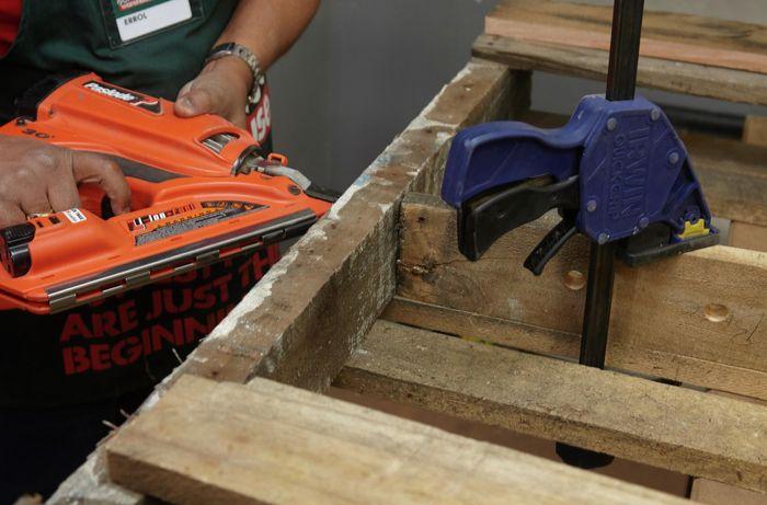 A person fixing a shelf into a timber frame using a nail gun