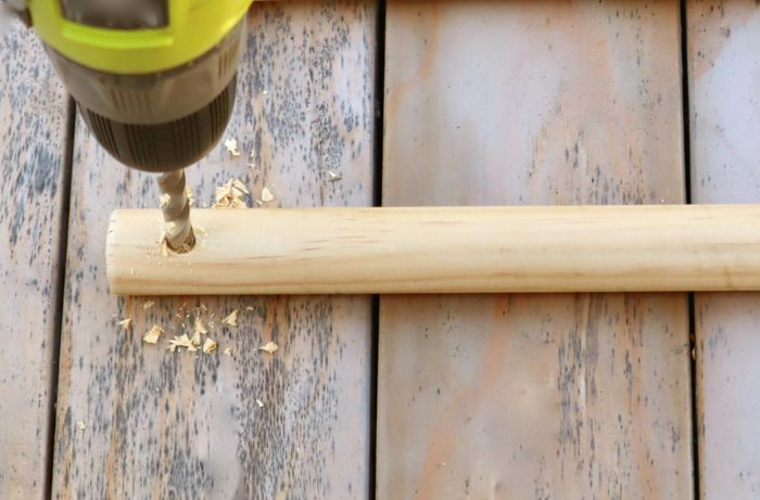 Close-up of a person drilling a hole in a dowel rod