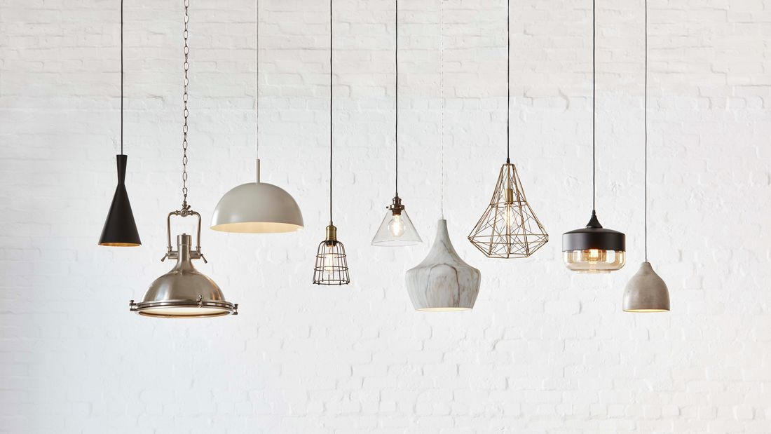 A selection of pendant lights hanging from the ceiling against a white brick wall.