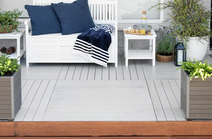 Outdoor entertaining area with white decking, planter boxes and chair.