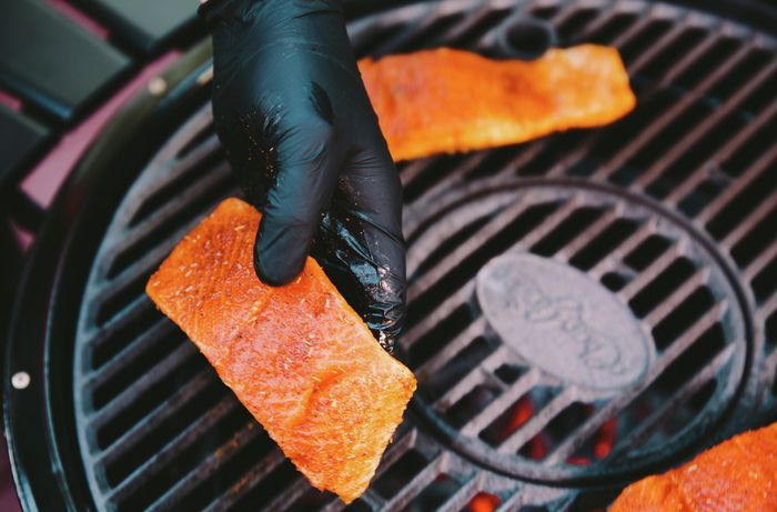Person holding a fillet of salmon coated in spices