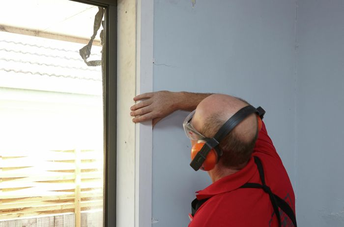 A person fitting architrave beside a window