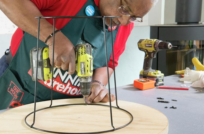 Person drilling holes into bottom of tabletop