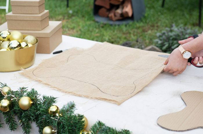 A person cutting through two sheets of hessian marked with the outline of a large bone