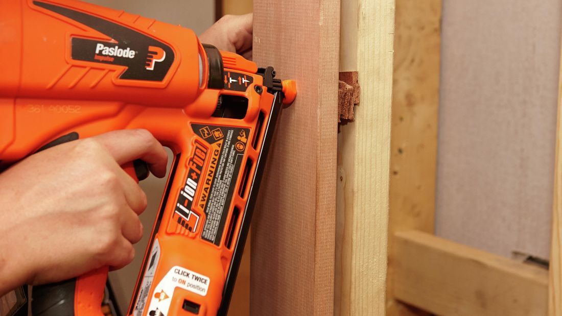 A person using a nail gun to attach a door frame to a wall stud with packers in between