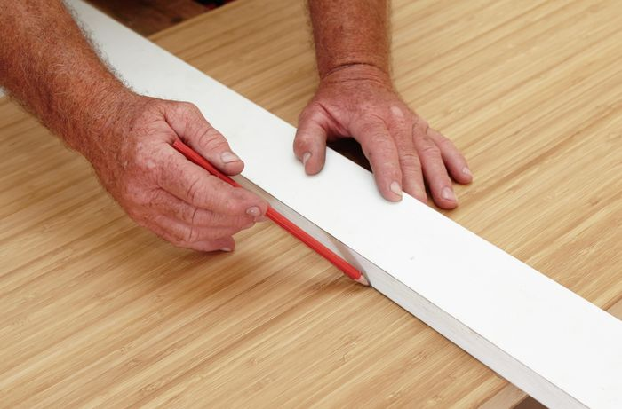 Person measuring and marking cut to be made on benchtop