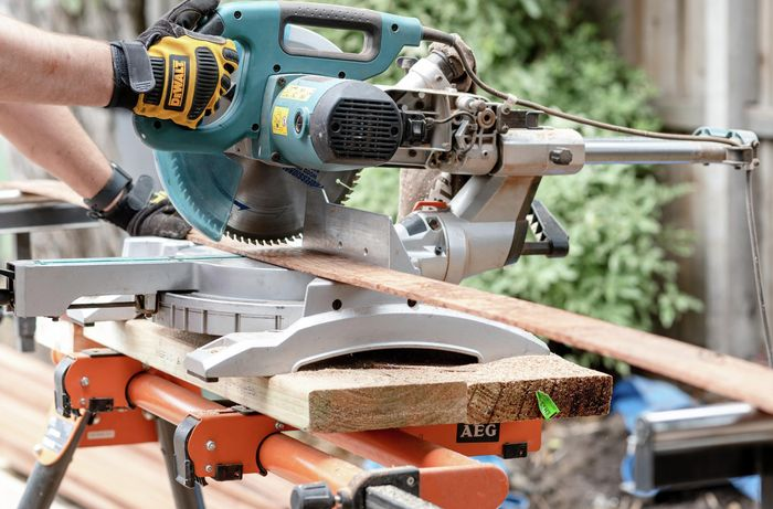 Person cutting timber edging with a circular saw.